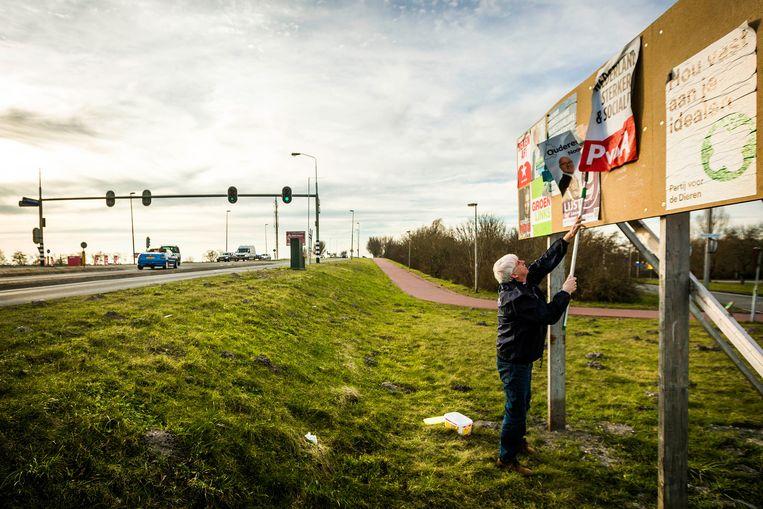 Jan van der Starre van de Ouderenpartij NH plakt een verkiezingsposter in Purmerend. Beeld Freek van den Bergh