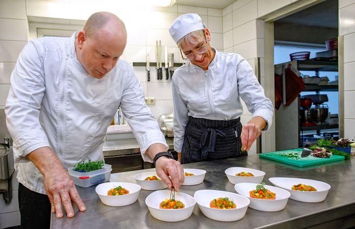 Chef Michael Somers en kok Petra Nieuwenweg bereiden het voorgerecht.