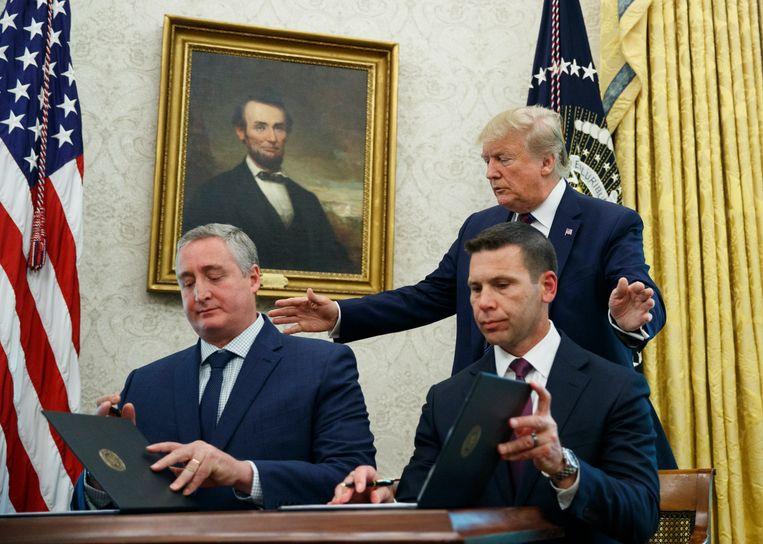 President Donald Trump kijkt toe hoe het akkoord wordt ondertekend door Kevin McAleenan en minister Enrique Degenhart van Guatemala