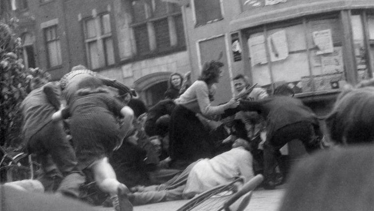 Amsterdammers zoeken dekking nadat Duitse soldaten het vuur openen op de Dam, 7 mei 1945. Beeld Bert Haanstra