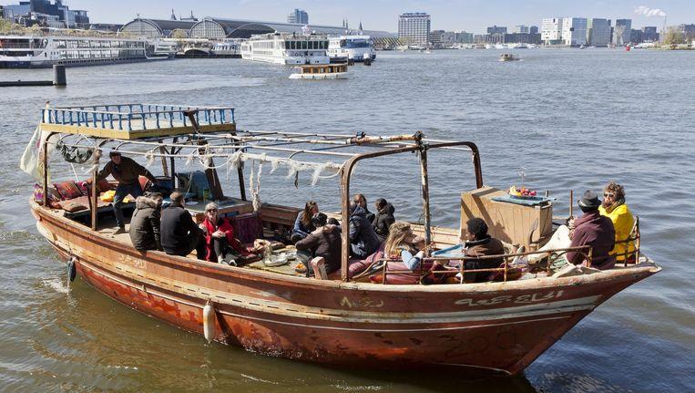 Oude en nieuwe Amsterdammers wisselen op het IJ verhalen uit. Beeld Roy del Vecchio