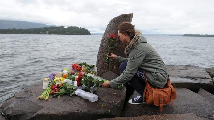 Een meisje legt bloemen neer ter nagedachtenis van de slachtoffers die vielen op het eiland Utoya (achtergrond).