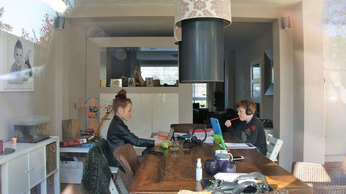 Zus en broer maken online schoolwerk in Eindhoven.