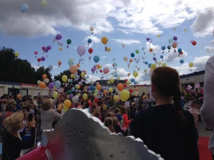 Leerlingen laten een ballon op met hun wensen voor een nieuwe school