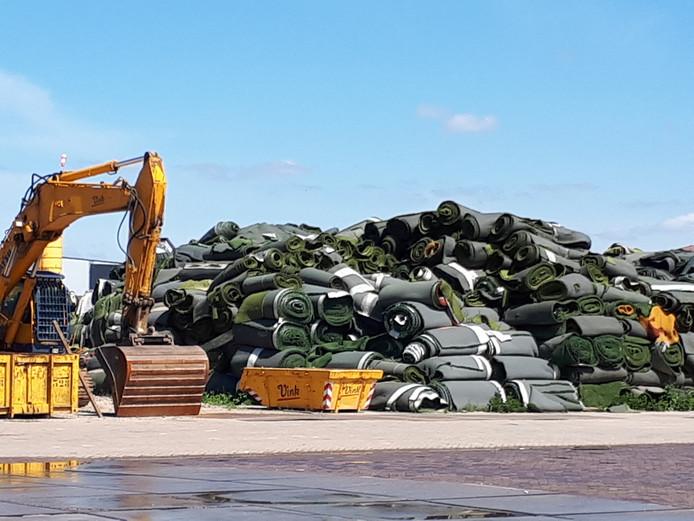 Op bedrijventerrein Harselaar liggen  enorme bergen door Vink ingenomen kunstgrasrollen opgestapeld. Zij getuigen nog steeds van de twijfelachtige aanpak van het Barneveldse bedrijf.