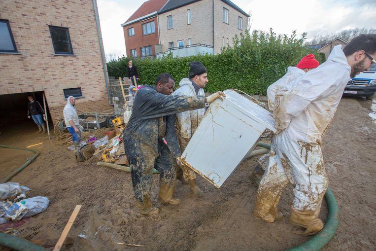 Arbeiders van een opkuisfirma halen de vernielde toestellen van Marleen Borremans en Peter Duponcheel naar buiten