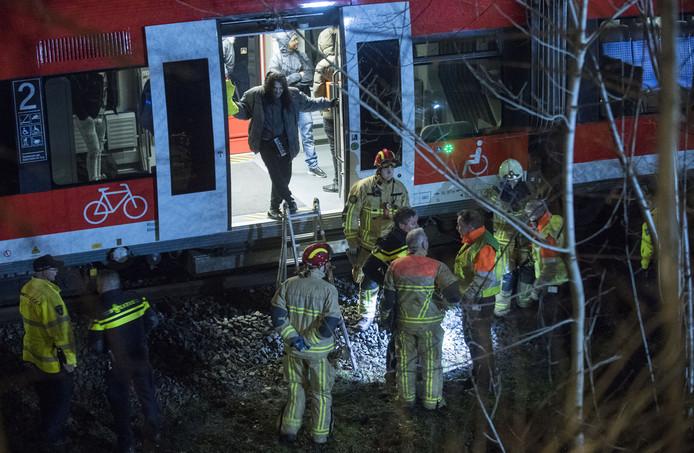 De brandweer helpt de inzittenden uit de trein.