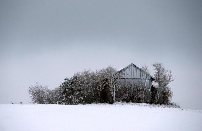 Een oude schuur lijkt zich te verstoppen onder de sneeuw, in het landschap van het Duitse Geretsried. Foto Karl-Josef Hildenbrand