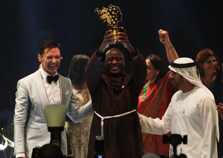 Peter Tabichi houdt zijn trofee omhoog. Rechts van hem staat sheikh Hamdan bin Mohammed Al Maktoum, kroonprins van Dubai.