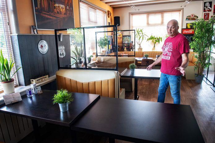 Henry van den Heuvel in zijn Hill's American Diner in Bergharen. Hij heeft alvast schermen geplaatst, al is nog onduidelijk of die worden goedgekeurd. De extra tafels voor serveren op 1,5 meter blijken niet nodig en gaan weer weg.