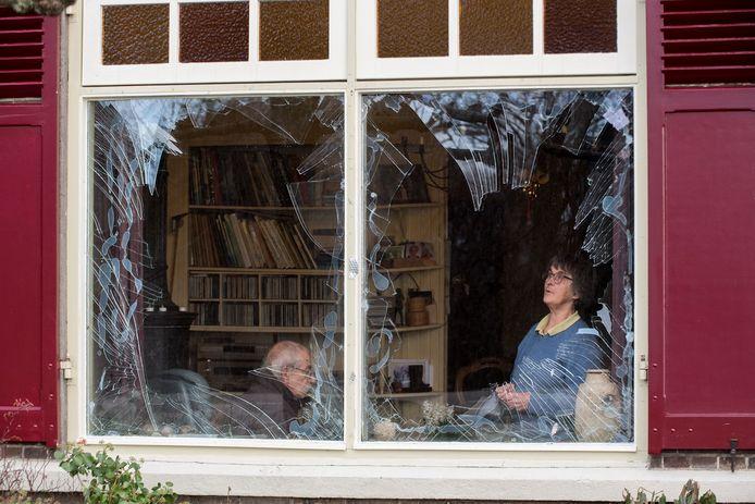 Foto uit 2019: Bas en Riet Hartman uit Opijnen voor een raam dat gesneuveld is door de vuurwerkbom. Door de explosie knalden tientallen ruiten van hun woning eruit: de daders stonden twee jaar na dato voor de rechter.