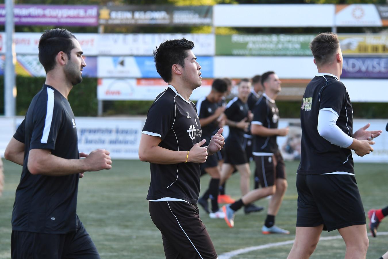 Jacky Chi (tweede links) tijdens een loopoefening bij JVC Cuijk. Geheel links Ali Özdemir.