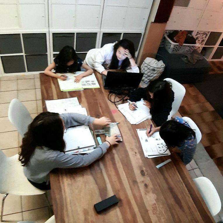 De meisjes maken samen hun huiswerk aan tafel.