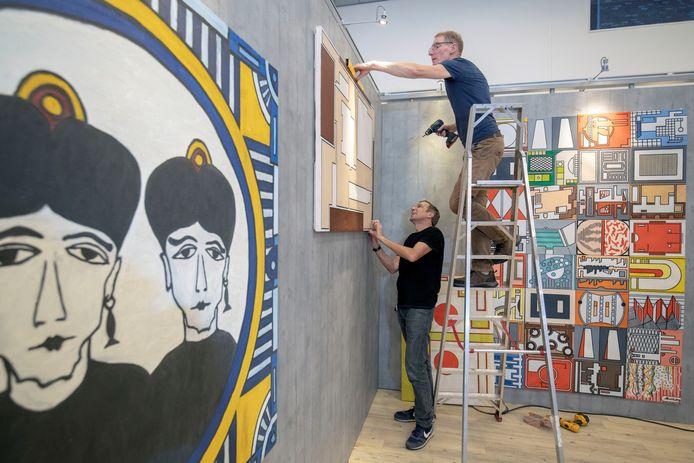 De inrichting van de expositie van kunstenaar Allard Budding in de Veenendaalse Cultuurfabriek. Op de trap de initiatiefnemer en voormalig vriend van de vorig jaar overleden kunstenaar, Hans Huitinck.