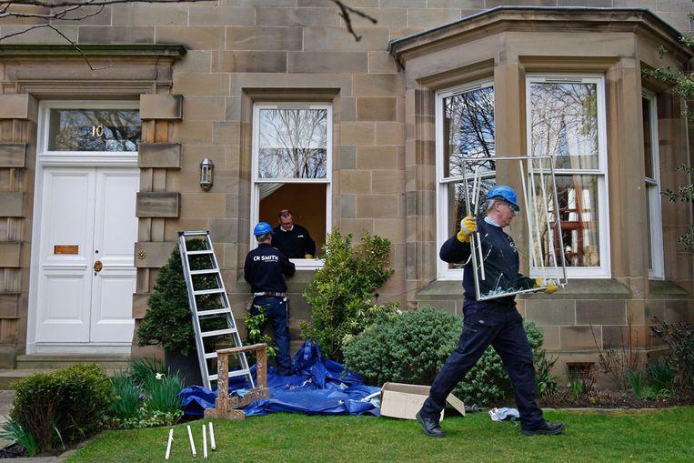 Glaszetters verwijderen de ingeslagen ruiten van de woning van Fred Goodwin. Beeld