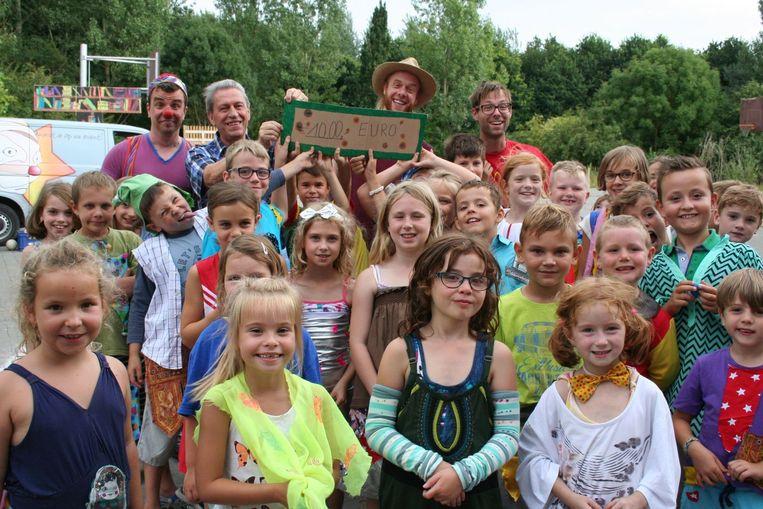 De kinderen overhandigen een zelfgemaakte cheque, ter waarde van 1.000 euro, aan de voorzitter van Mediclowns.