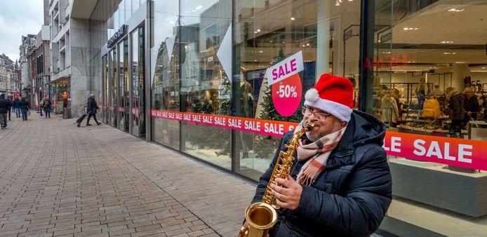 Een straatmuzikant speelt zijn deuntje voor de Hudson's Bay in de Tilburgse Heuvelstraat.