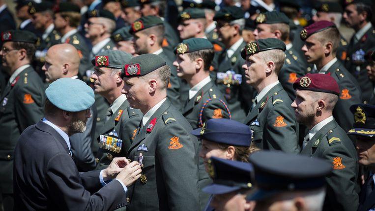 Veteranen krijgen medailles opgespeld tijdens de landelijke Veteranendag in Den Haag Beeld anp