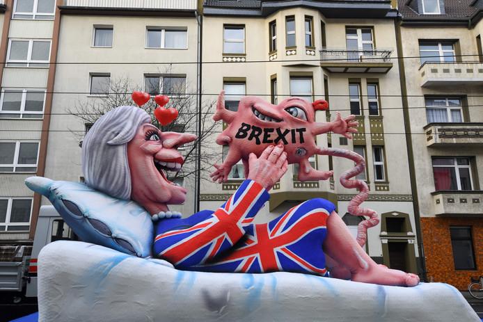 Bij de carnavalsoptocht in Düsseldorf rijdt een praalwagen voorbij waarmee de draak wordt gestoken met de Britse premier Theresa May die een Brexit baart. Foto Patrik Stollarz