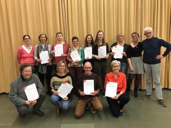 """Deelnemers van de cursus """"Eerste Hulp"""" en """"Helper"""" poseren trots met hun brevet op de foto."""