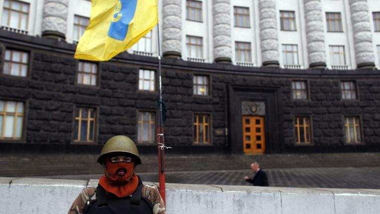 Een demonstrant bewaakt het regeringsgebouw in Kiev. Beeld ap