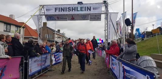Lopers druppelen binnen bij de finish van de Wandelmarathon.