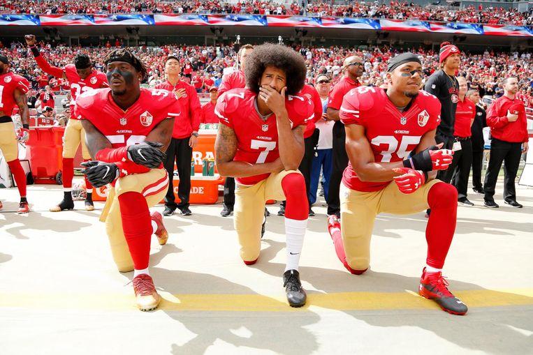 Colin Kaepernick, midden, knielt samen met twee teamgenoten tegen raciale ongelijkheid in Amerika tijdens het spelen van het Amerikaanse volkslied voor de wedstrijd.