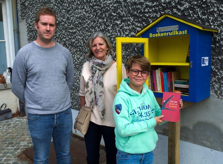 Andreas Van den Bergh (11) mocht als eerste van de nieuwe boekenruilkast 'proeven'. Voormalig bibliothecaris Marijke Dierckx en assistent Jeroen De Lathouwer kijken goedkeurend toe.