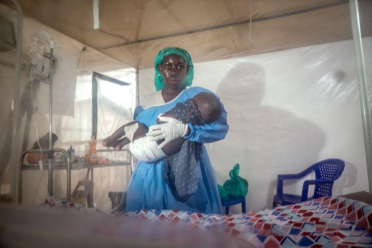 Neema heeft de zorg op zich genomen van Dieugrand, een jongetje dat lijdt aan ebola. Samen met enkele andere oud-patiënten is Neema verpleegster in het stadje Beni in Congo. Beeld Sven Torfinn