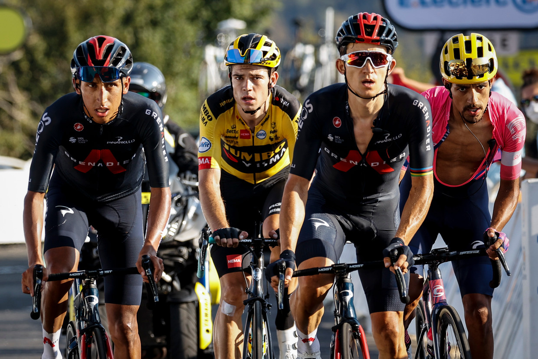 Wout van Aert (midden) heeft op de Colombier weer het nodige kopwerk gedaan en komt uitbollend over de finish, in het kielzog van de verliezer van de dag Egan Bernal (links). Beeld BELGA