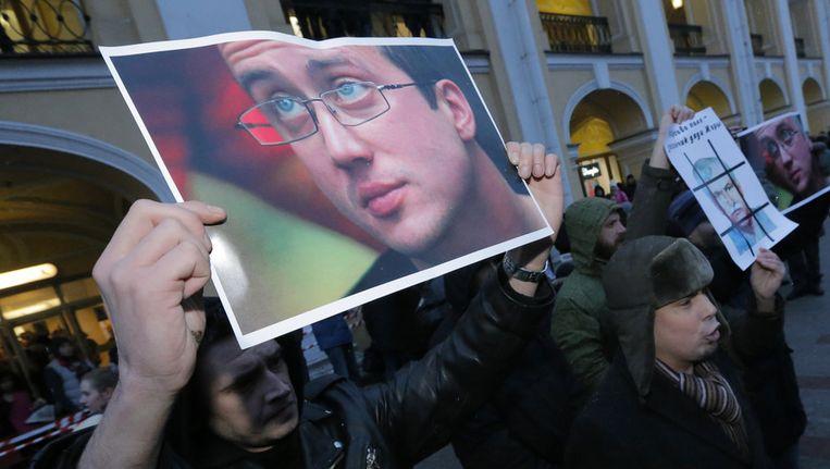 Demonstranten in Sint Petersburg met een portret van Alexander Dolmatov Beeld ap