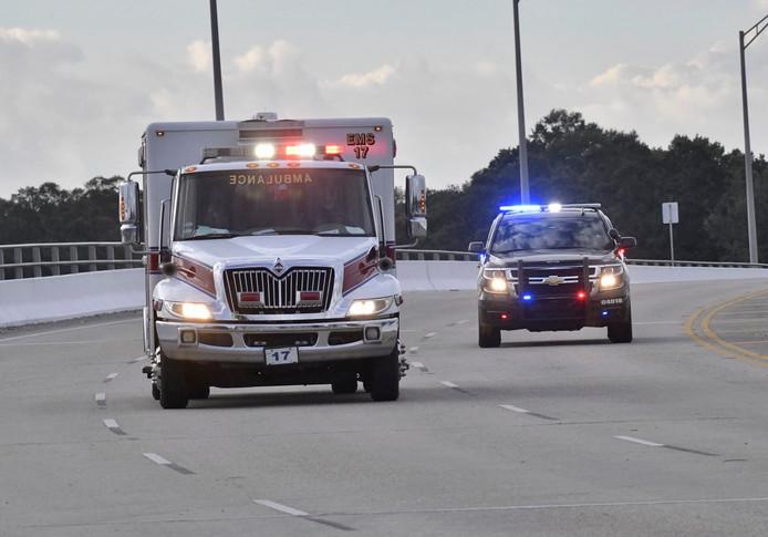 Een politieauto escorteert een ambulance met daarin een van de gewonden van de schietpartij op de Amerikaanse marinebasis.