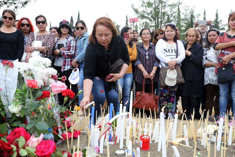Vrouwen leggen bloemen neer en steken kaarsen aan ter nagedachtenis aan de slachtoffers.