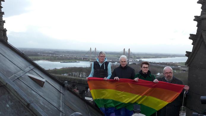 Rein van Willigen, de predikanten Jos de Heer en Trijnie Bouw en pastor Bertus Bus (vlnr) met de regenboogvlag op de toren van de Sint-Maartenskerk in Zaltbommel