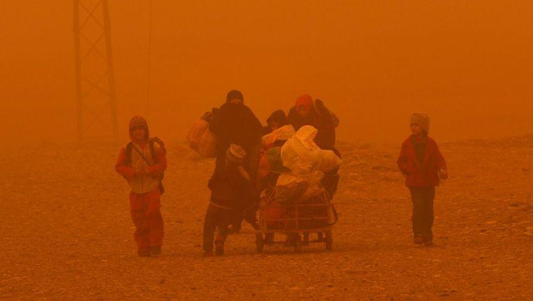 Door de zandstorm vlucht een groep van Mosul naar Gogjali. Beeld afp