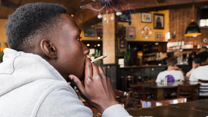 Een jongen rookt een joint bij coffeeshop The Grass Company aan de Tilburgse Spoorsingel