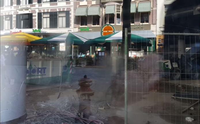 De l;eg terrassen, gespiegeld gezien in het raam van de V&D, waar binnen wordt geslootp.