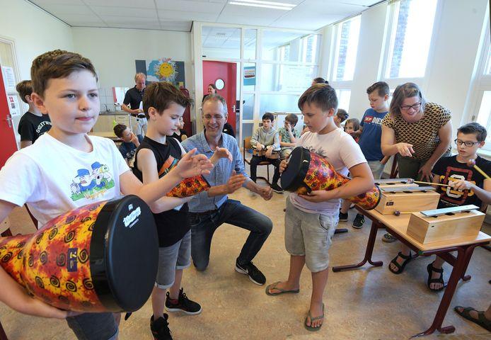 Tiel Muziekles voor kinderen met van links naar rechts de leerlingen Timo, Flynn en Bram met tussen hen in Alwin de Vries.