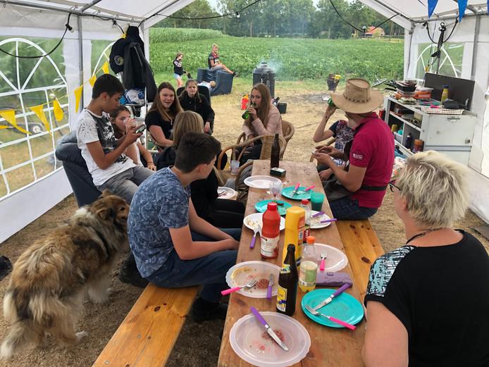 Kampeerfeest in Geesteren, tijdens het diner helpen ouders een handje mee.