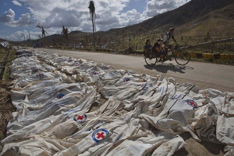 Honderden lijken liggen in Tacloban langs de kant van de weg. Forensische experts zullen ze registreren en begraven in een massagraf. Beeld ap