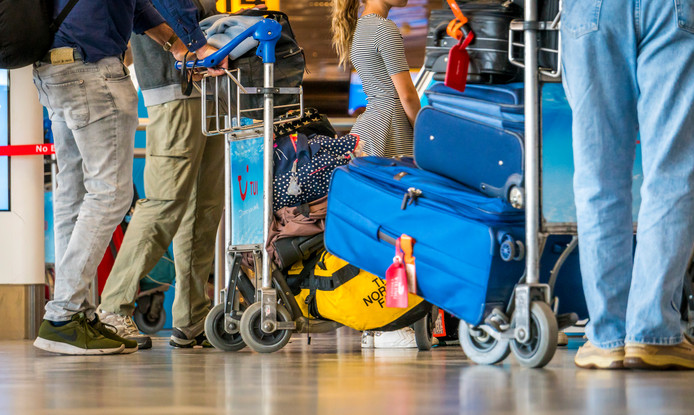 Passagiers slepen heel wat bagage mee op luchthaven Schiphol.