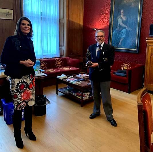 Hans Blommaart met het beeldje en staatssecretaris Barbara Visser in het ministerie van Defensie in Den Haag.