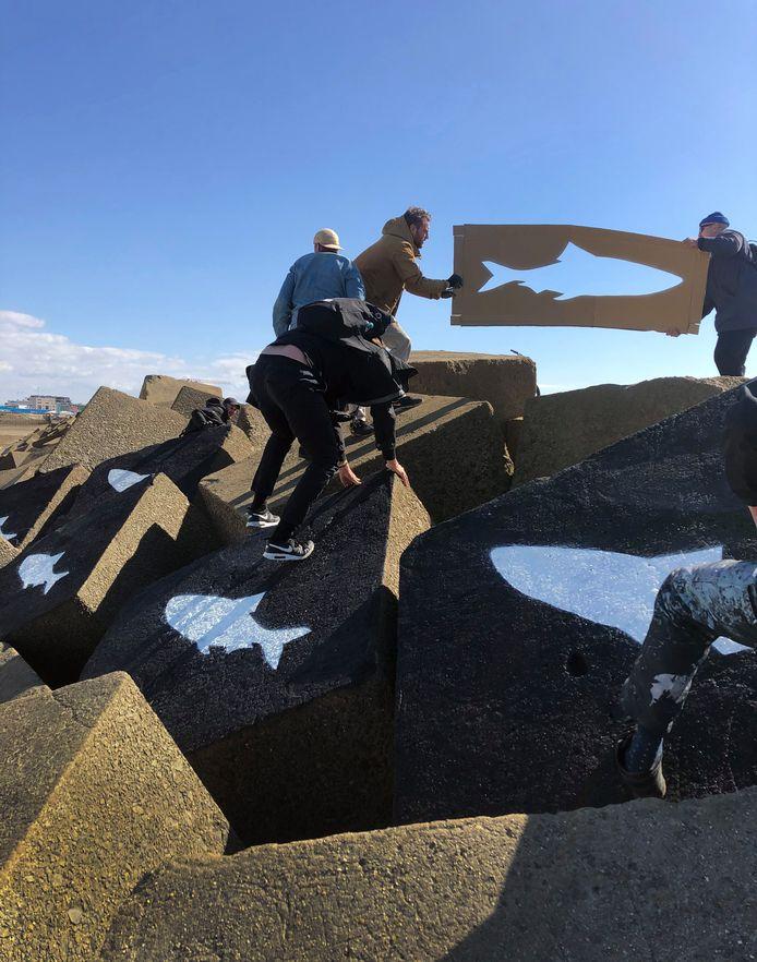 Surfvrienden van de afgelopen maandag overleden surfers plaatsen als eerbetoon vijf witte haringen op vijf zwart gespoten basaltblokken vlak bij de plek waar de jonge surfers vermoedelijk zijn verdronken.
