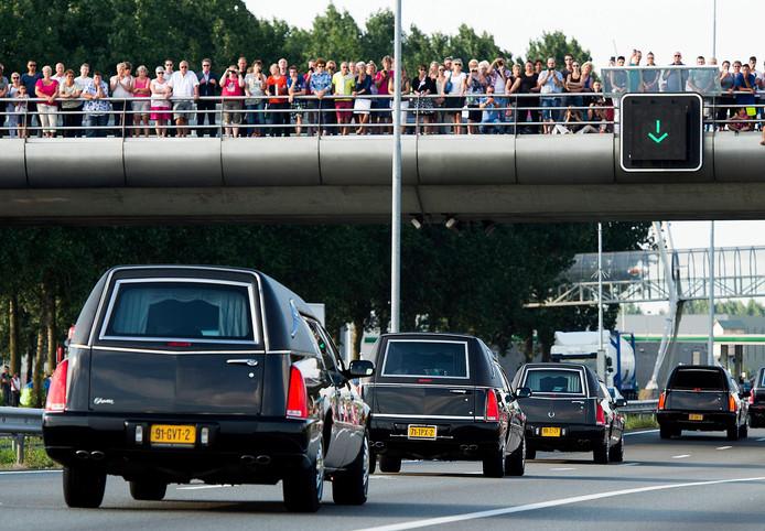Honderden mensen kijken op de viaducten naar de voorbijtrekkende rouwstoet.