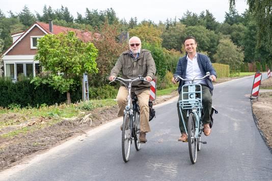 """Wethouder Ruud van Leeuwen (links) en beleidsmedewerker Frans Mosterman testen het nieuwe asfalt. ,,Voor de bovenlaag afhankelijk van de onderlaag. Je kunt op een bestaande asfaltweg niet zomaar beton gebruiken."""""""