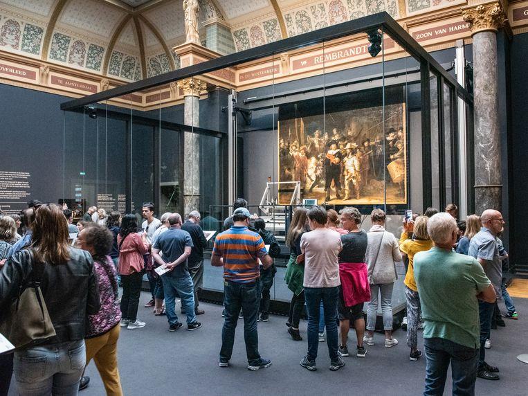 Bezoekers van het Rijksmuseum aanschouwen het beroemde schilderij 'de nachtwacht' vanachter glas.  Beeld Simon Lenskens
