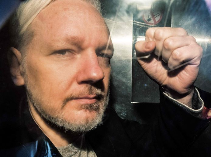 Assange toont zich strijdbaar vanuit een politiewagen op weg naar de rechtbank.