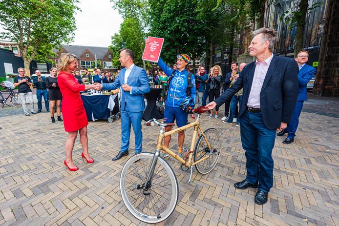 Fietskoerier Karen Poot houdt triomfantelijk het Utrechtse bidbook voor het Songfestival omhoog op het Domplein. Jaarbeurs-directeur Jacqueline Bakker en wethouder Klaas Verschuure schudden elkaar de hand.