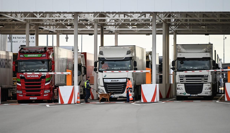 Een medewerker van Eurotunnel controleert met zijn hond vrachtwagens op weg naar het Verenigd Koninkrijk.