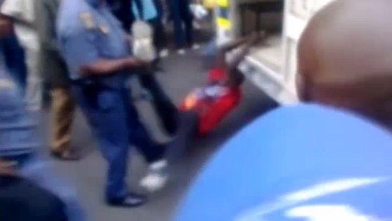Afrikaanse man wordt vastgebonden aan politiebusje Beeld Screenshot uit filmpje